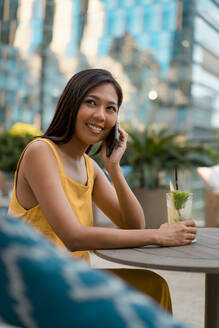 Portrait of smiling woman on the phone sitting in a cafe with a drink - MAUF03153