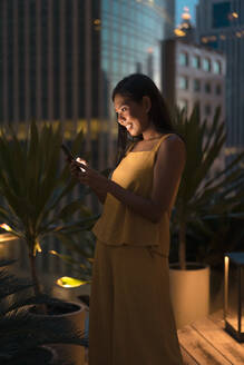 Happy woman standing on roof terrace at dusk looking at cell phone, Bangkok, Thailand - MAUF03156
