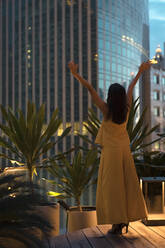 Back view of happy woman standing on roof terrace raising hands, Bangkok, Thailand - MAUF03159