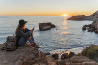 Young woman using smartphone on beach during sunset, Ibiza - AFVF04290
