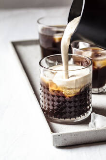 Frothed milk is poured over iced coffee - SBDF04115