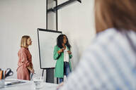 Businesswoman leading a presentation at flip chart in conference room - ZEDF02719