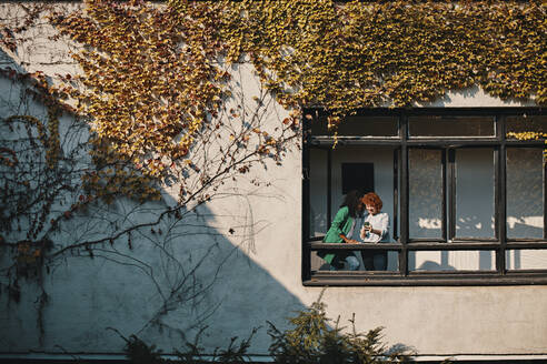 Two businesswomen with smartphone standing at the window of an office building - ZEDF02770