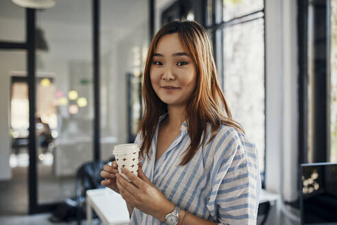 Portrait of businesswoman having a coffee break in office - ZEDF02776