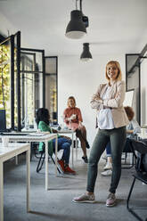 Portrait of confident pregnant businesswoman in office with colleagues in background - ZEDF02785