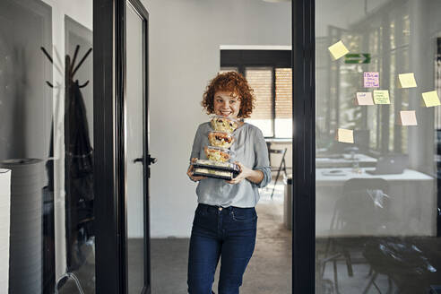 Smiling businesswoman serving takeaway food in office - ZEDF02794