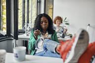 Businesswoman having lunch break in office with feet on desk - ZEDF02800