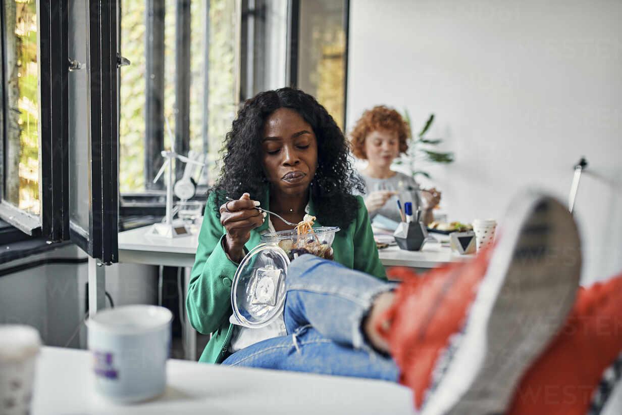 Businesswoman having lunch break in office with feet on desk - ZEDF02800 - Zeljko Dangubic/Westend61