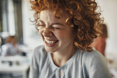 Portrait of a laughing businesswoman with closed eyes in office - ZEDF02821