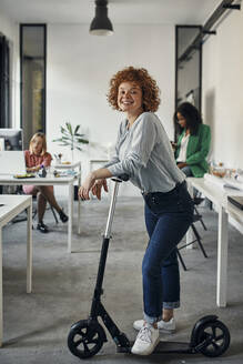 Portrait of a smiling businesswoman with kick scooter in office - ZEDF02827