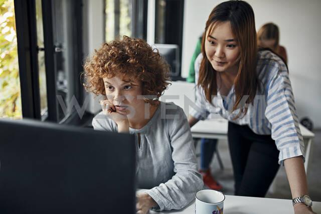 Two businesswomen looking at desktop pc in office - ZEDF02842 - Zeljko Dangubic/Westend61