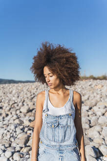 Portrait of young woman on empty beach, looking up - AFVF04302