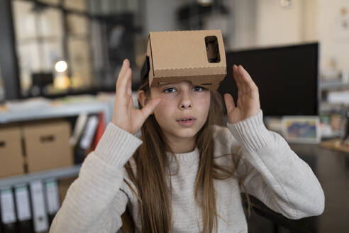 Girl with cardboard VR glasses in office - GUSF02695