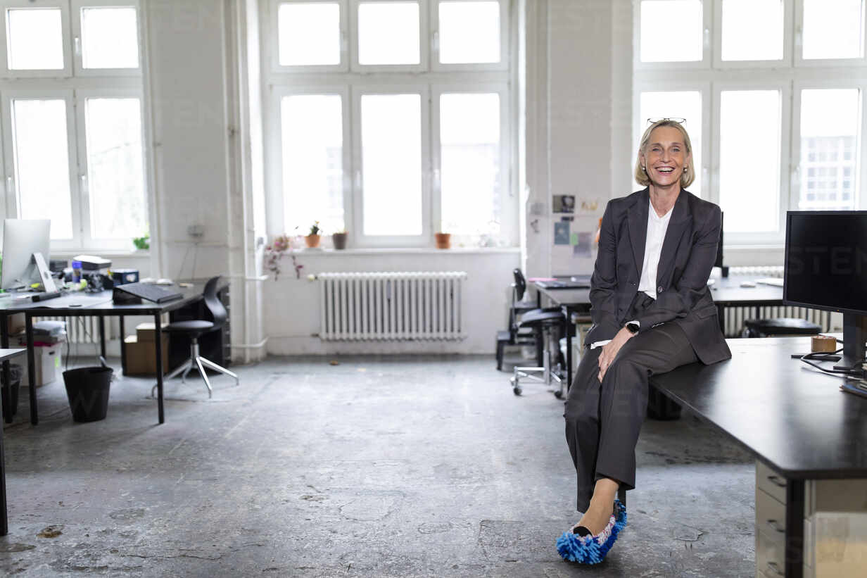 Happy mature businesswoman wearing cleansing slippers in office - GUSF02698 - Gustafsson/Westend61