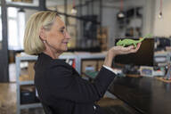 Mature businesswoman holding chameleon figurine in office - GUSF02701