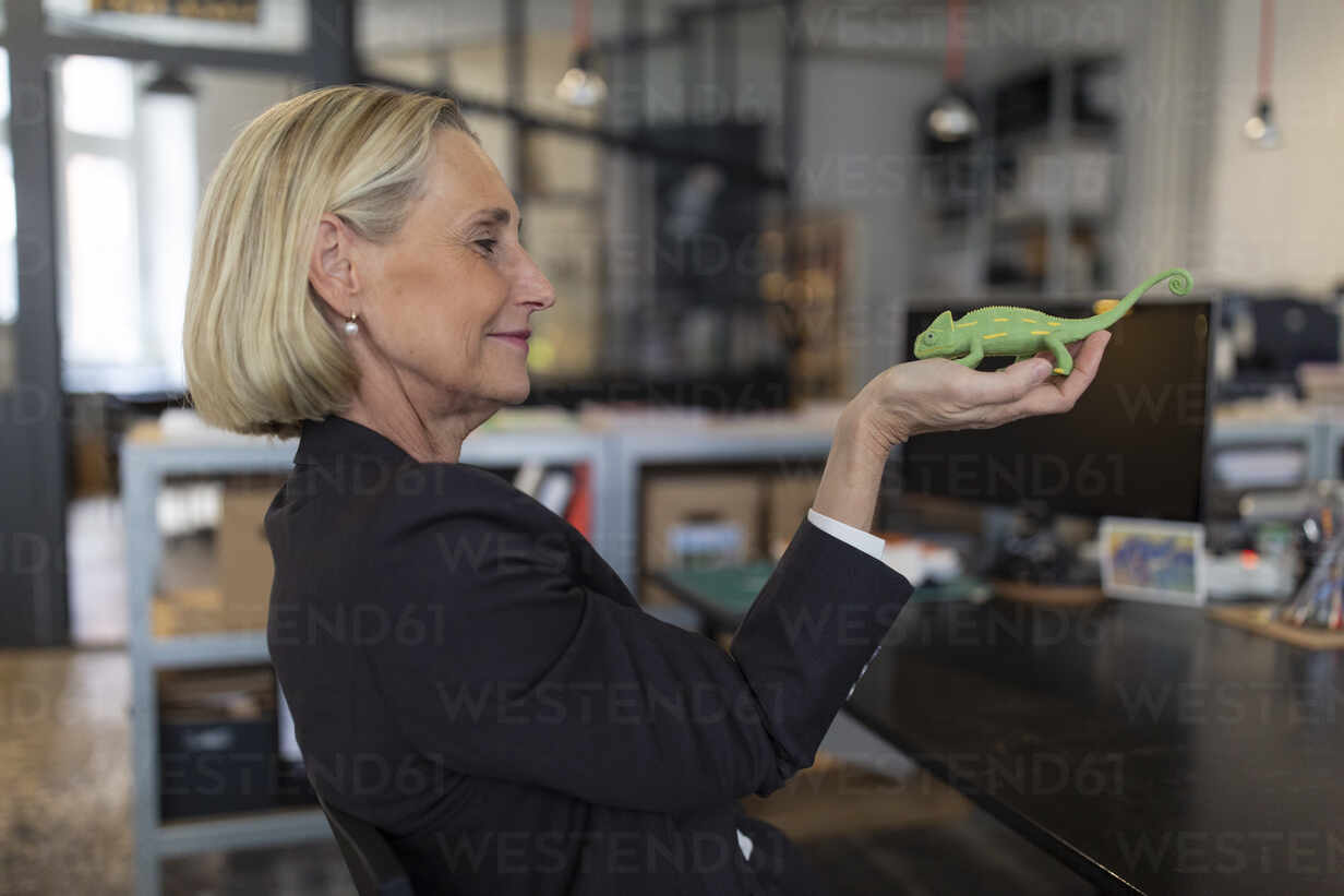 Mature businesswoman holding chameleon figurine in office - GUSF02701 - Gustafsson/Westend61