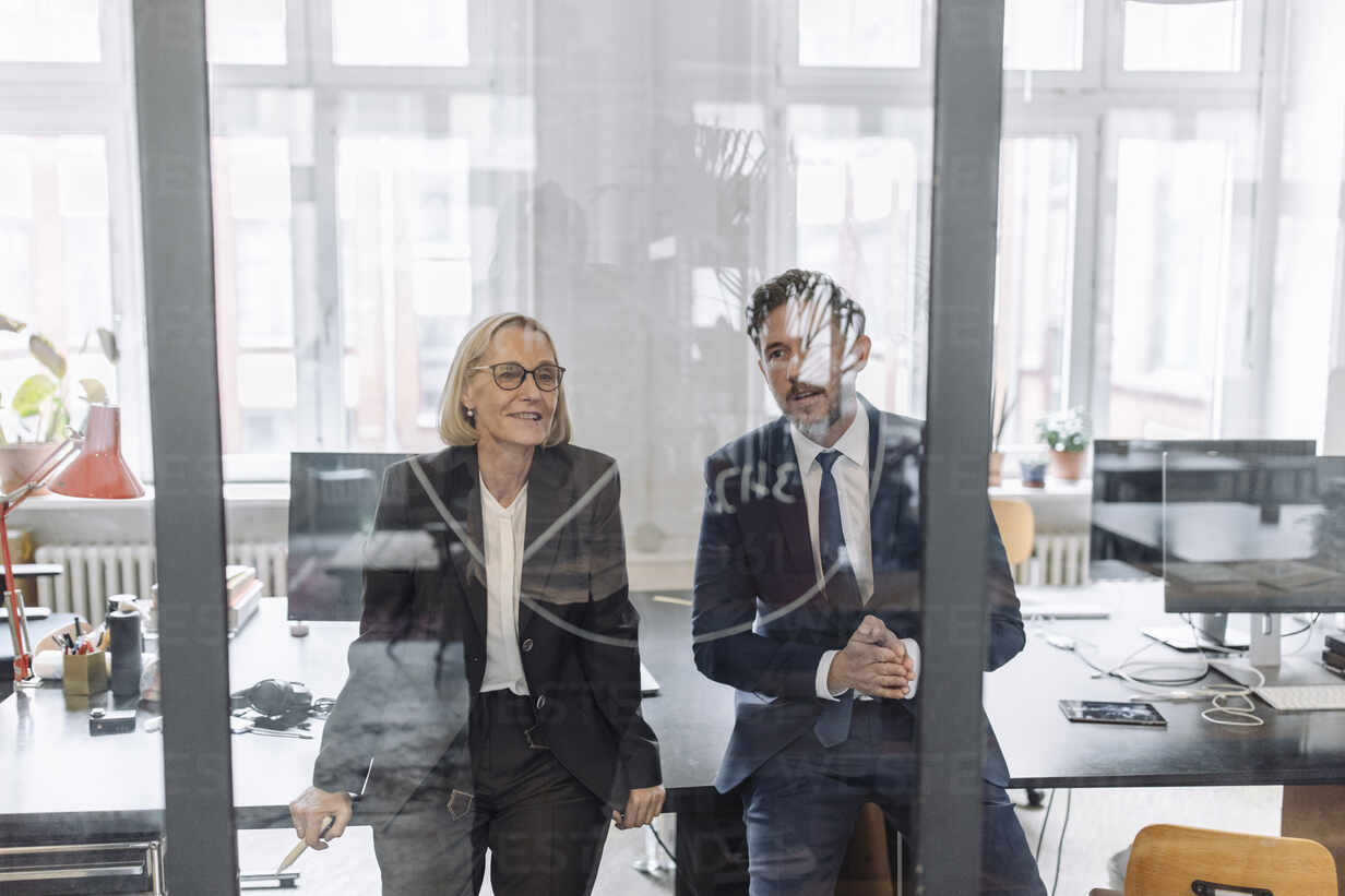 Businessman and businesswoman looking at drawing on glass pane in office - GUSF02704 - Gustafsson/Westend61