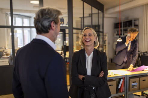 Smiling businesswoman and businessman talking in office - GUSF02713