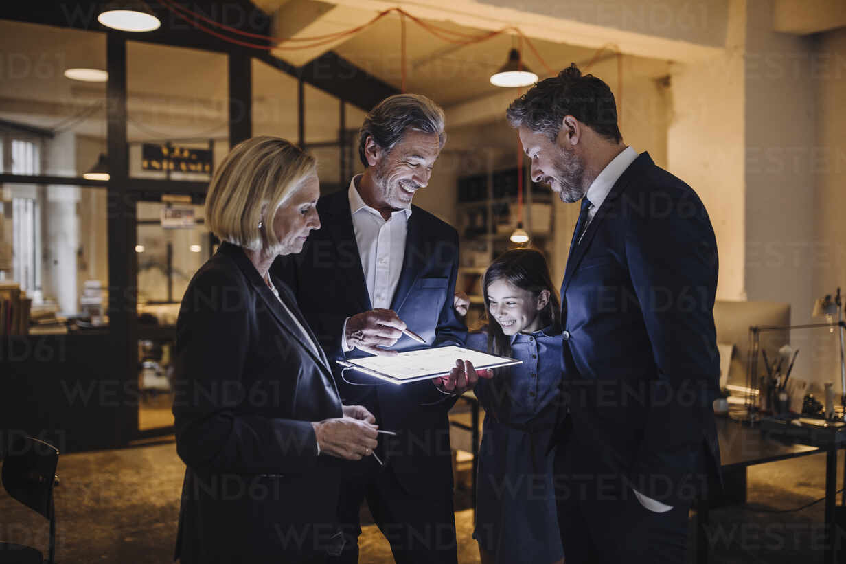 Business people and girl looking at shining tablet in office - GUSF02719 - Gustafsson/Westend61