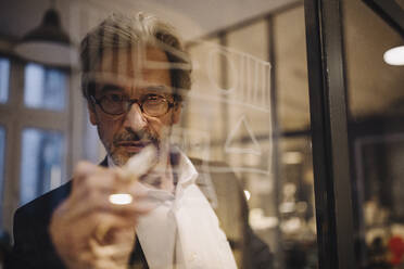 Senior businessman drawing on glass pane in office - GUSF02740