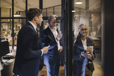 Smiling businesswoman and two businessmen working on drawing on glass pane in office - GUSF02743