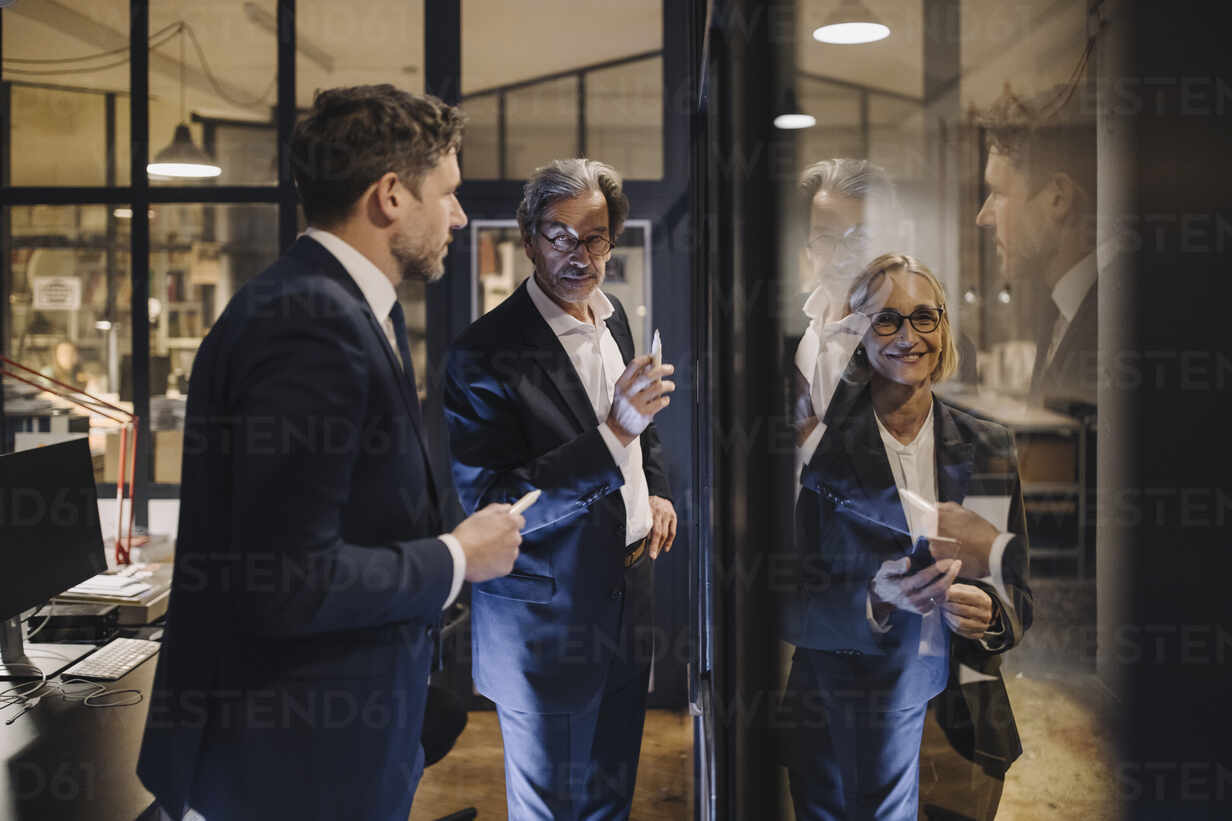 Smiling businesswoman and two businessmen working on drawing on glass pane in office - GUSF02743 - Gustafsson/Westend61