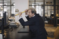 Angry senior businessman with giant pencil at desk in office - GUSF02776