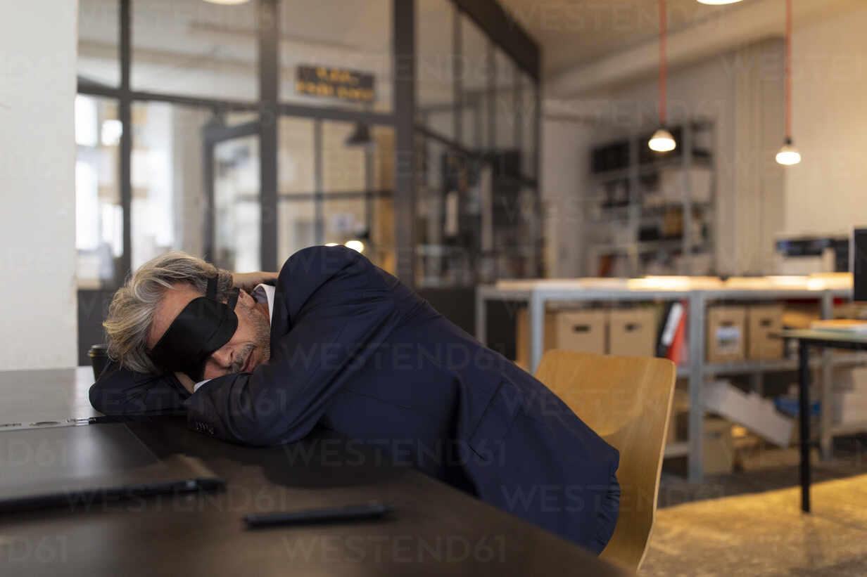 Senior businessman having a power nap at desk in office - GUSF02779 - Gustafsson/Westend61
