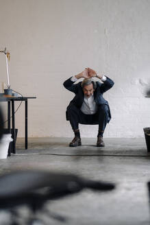 Senior businessman doing gymnastics in office - GUSF02806