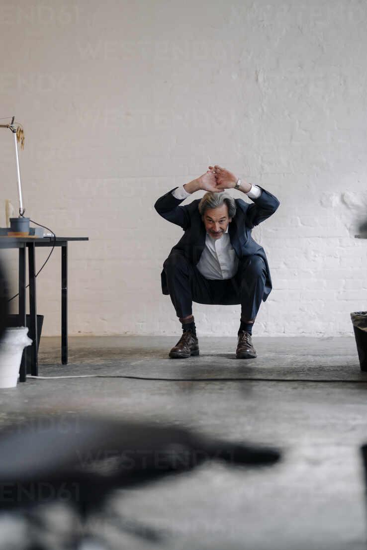 Senior businessman doing gymnastics in office - GUSF02806 - Gustafsson/Westend61