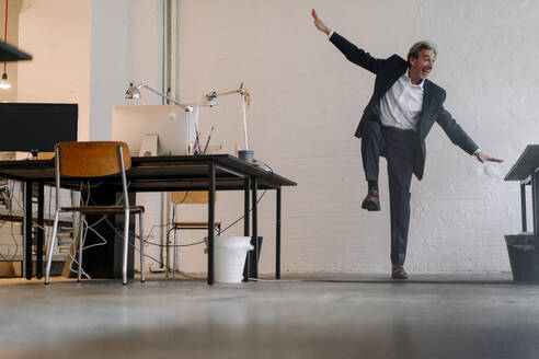 Happy senior businessman doing gymnastics in office - GUSF02809