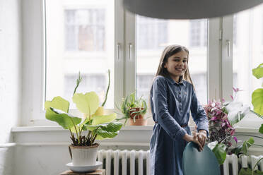 Happy girl with standing at the window in office - GUSF02875