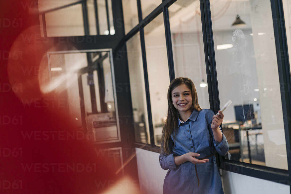 Happy girl drawing on glass pane in office - GUSF02878 - Gustafsson/Westend61