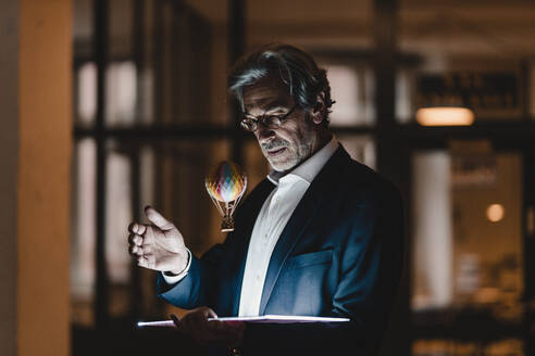 Senior businessman with tablet and floating hot-air balloon in office - GUSF02899