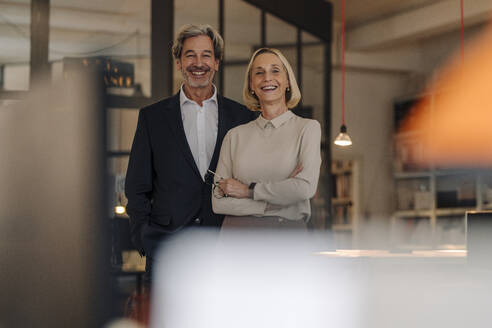 Portait of smiling businessman and businesswoman in office - GUSF02902