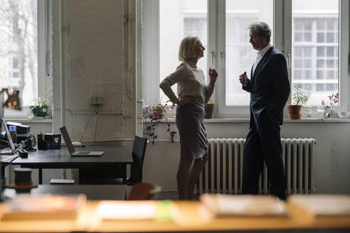 Businessman and businesswoman talking at the window in office - GUSF02911