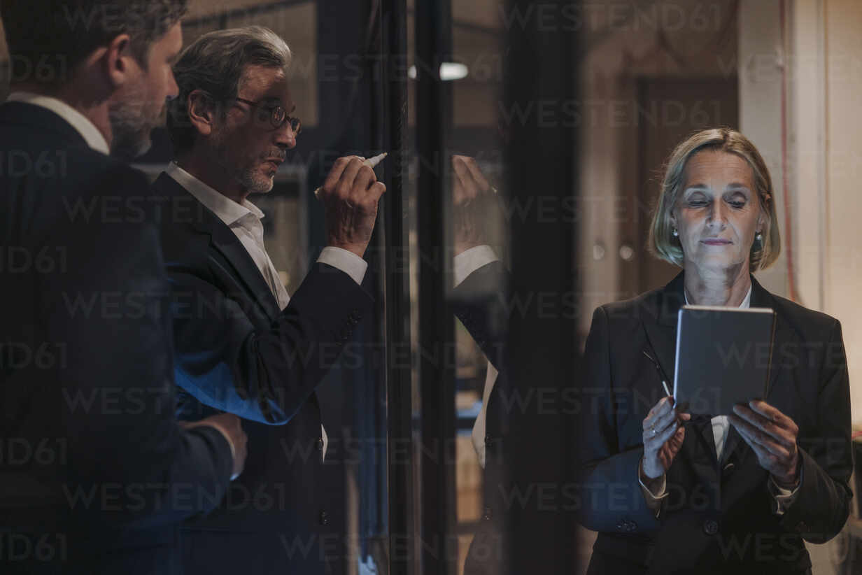 Businesswoman using tablet and two businessmen working on drawing on glass pane in office - GUSF02923 - Gustafsson/Westend61