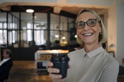 Portrait of happy mature businesswoman having a coffee break in office - GUSF02932