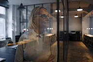Mature behind glass pane businesswoman in office - GUSF02935