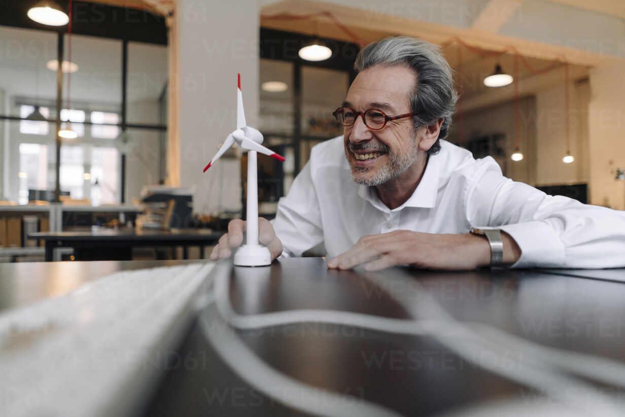Happy senior businessman with wind turbine model in office - GUSF02938 - Gustafsson/Westend61