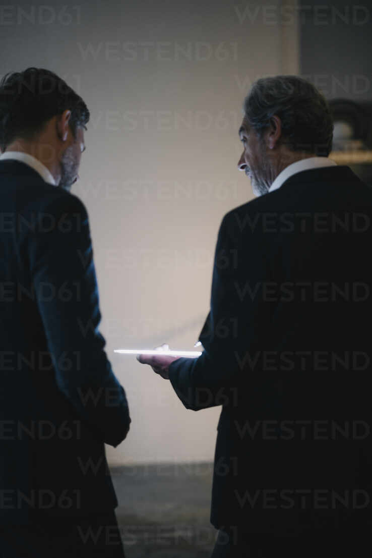 Two businesssmen with shining tablet talking in office - GUSF02944 - Gustafsson/Westend61