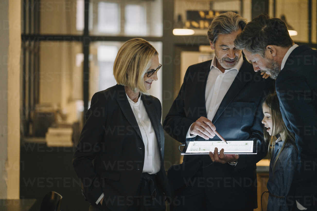 Business people and girl looking at shining tablet in office - GUSF02947 - Gustafsson/Westend61