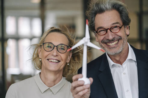 Portrait of happy businessman and businesswoman holding wind turbine model in office - GUSF02950