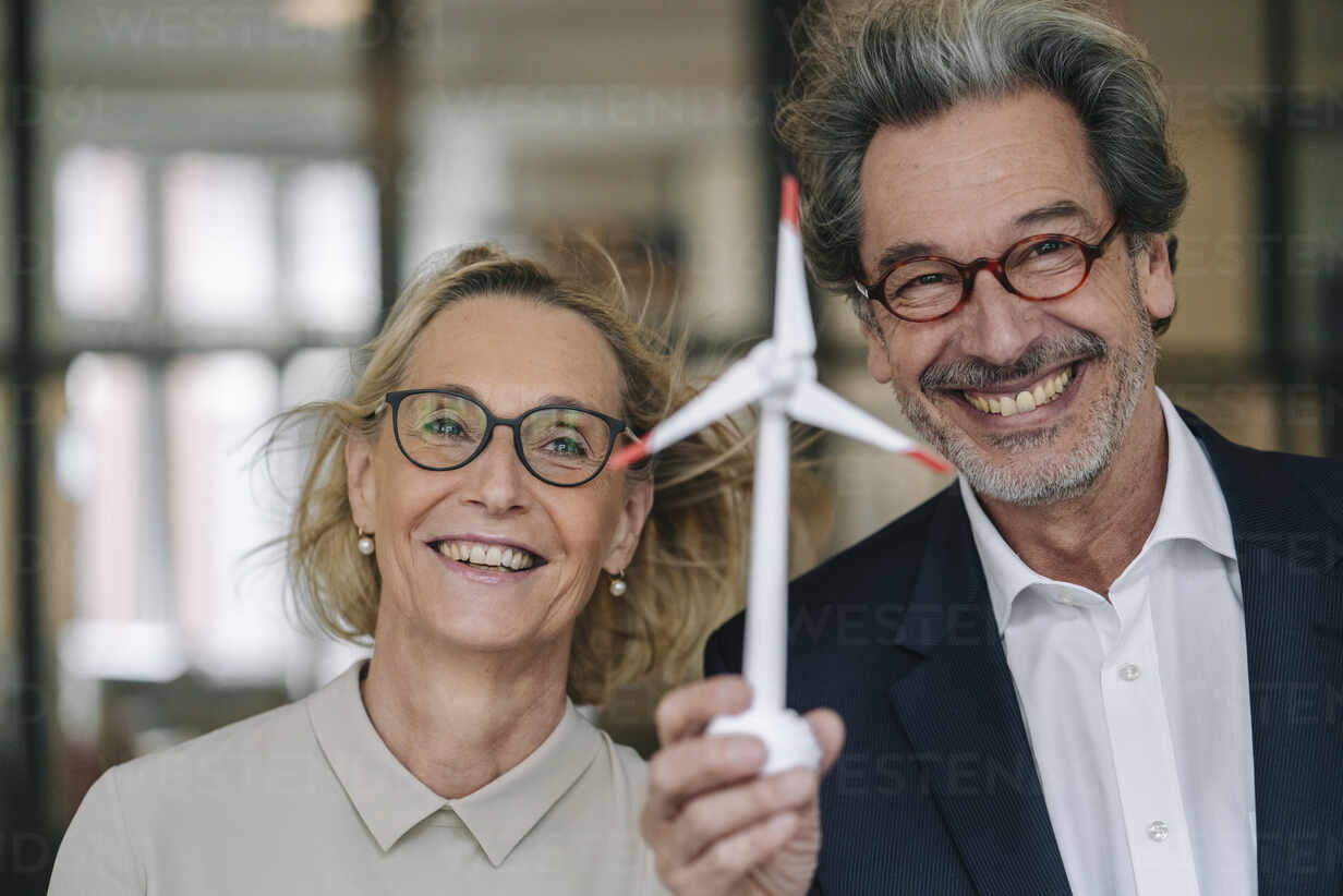 Portrait of happy businessman and businesswoman holding wind turbine model in office - GUSF02950 - Gustafsson/Westend61