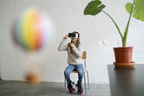 Girl with VR glasses and hot-air balloon in office - GUSF02965