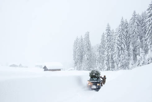 Austria, Salzburger Land, Lammertal, Man attaching Christmas tree to car roof on snowy road - HHF05578