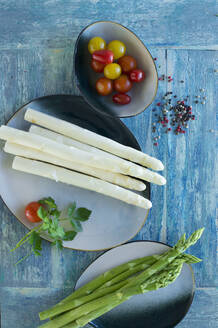White and green asparagus on rustic wooden background, yellow tomatoes, red tomatoes, colored pepper, parsley - ASF06537