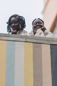Portrait of two smiling friends leaning on balustrade looking down to viewer - DLTSF00297