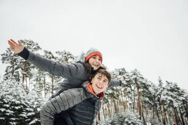Portrait of smiling young man giving his happy girlfriend a piggyback ride in winter forest - OCMF00928
