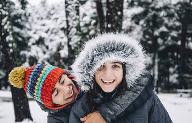 Portrait of happy young couple in winter forest - OCMF00931